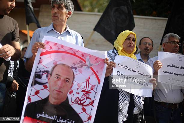 Palestinian journalists hold placards and banners during a demonstration on April 25 outside the Red Cross offices in Gaza city in support of their...