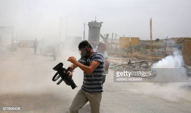 Palestinian journalists run for cover from tear gas canisters fired by Israeli forces during a demonstration in support of Palestinian journalists on...