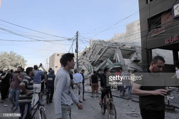 Palestinian journalists stand in shock following the destruction of Jala Tower, which was housing international press offices, by an Israeli...