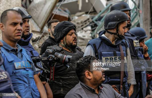 Palestinian journalists stand in shock following the destruction of Jala Tower, which was housing international press offices, in the Gaza Strip. The...
