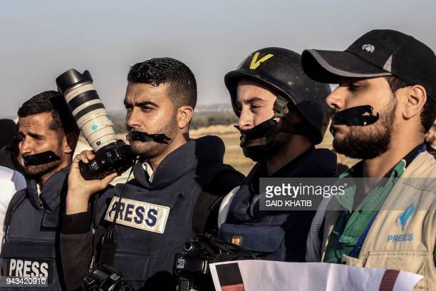 TOPSHOT Palestinian journalists tape their mouths shut during a protest against the killing of fellow journalist Yasser Murtaja near the IsraelGaza...