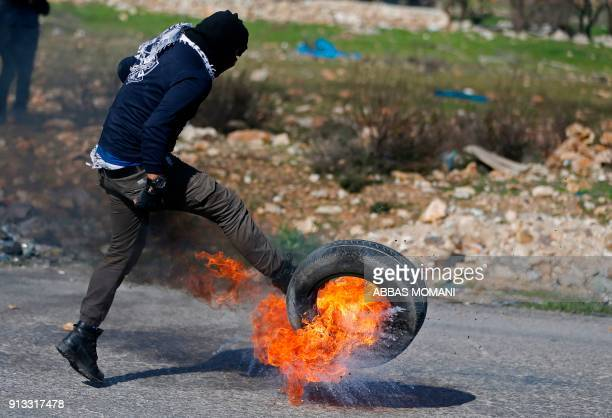 Palestinian kicks a burning tire during clashes with Israeli forces on February 2 2018 in Ramallah in the Israelioccupied West Bank