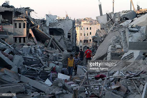 Palestinian kids inspect their remains from the rubble of destroyed houses during the 72hour humanitarian ceasefire in Shujaya neighborhood Gaza on...