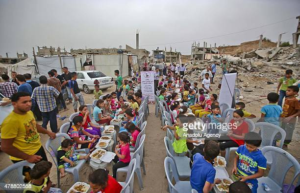 Palestinian kids play amongst the rubble of destroyed houses during the Ramadan activities organized by the nongovernmental organization in...