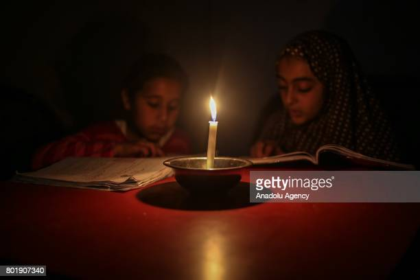 Palestinian kids read book by candle light due to power cut at the Jabalia Camp in Gaza City Gaza on June 27 2017 2 million people living in Gaza...