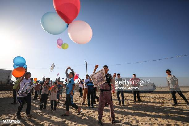 Palestinian kids release balloons as they hold placards regarding the resistance during an event organized by International Committee for Breaking...
