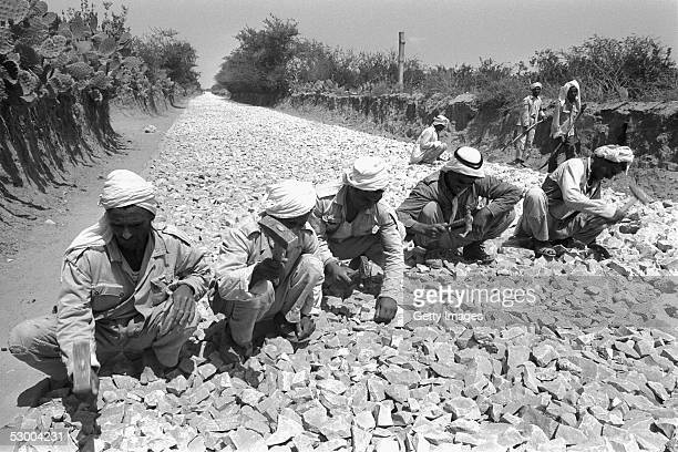 Palestinian laborers employed by the Israeli army's Civil Administration lay a road some two years after the SixDay War June 10 near Khan Younis Gaza...