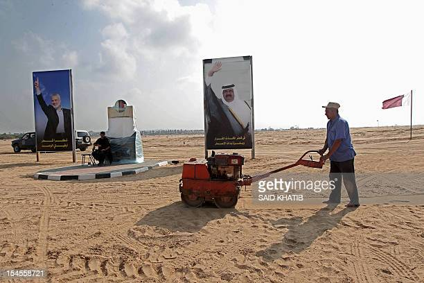 A Palestinian labourer works near posters of Hamas prime minister Ismail Haniya and Qatar's Emir Sheikh Hamad bin Khalifa alThani at the construction...