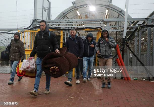 Palestinian labourers enter Israel to work through a checkpoint between the West Bank city of Hebron and Beersheva while carrying blankets and...