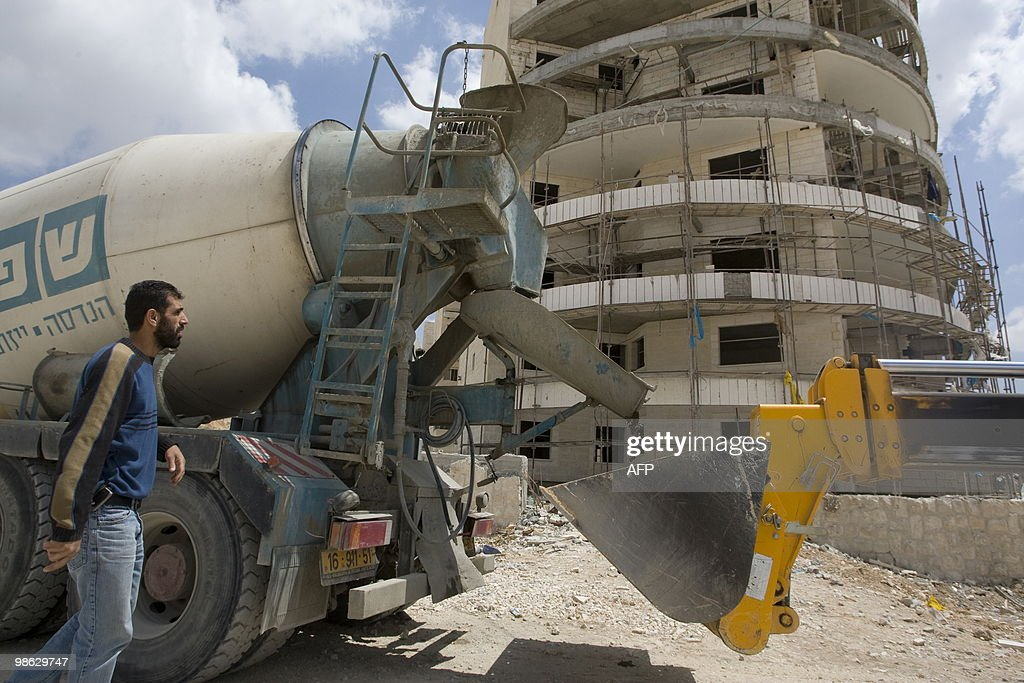 Palestinian labourers work on a new hous