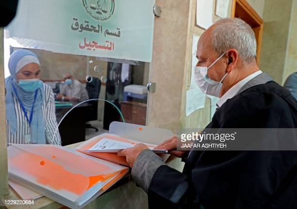 Palestinian lawmaker presents documents at the court where chief of the National Assembly of Independents Munib al-Masri filed a lawsuit against...