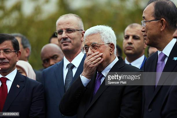 Palestinian leader Mahmoud Abbas pauses moments before the Palestinian flag is raised for the first time at the United Nations headquarters on...