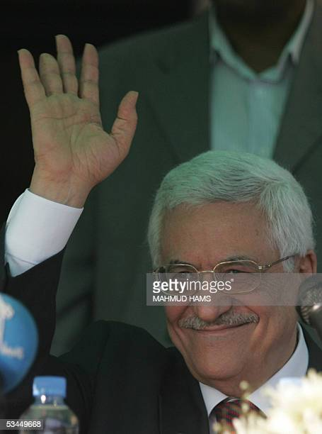 Palestinian leader Mahmud Abbas waves during a rally for Palestinians who have been disabled during the course of the five-year intifada, outside his...