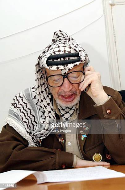 Palestinian leader Yasser Arafat speaks on the cell phone to French demonstrators in his compound on the second anniversary of the intifada or...