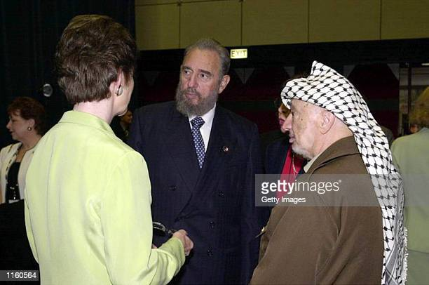 Palestinian leader Yasser Arafat talks with Cuban President Fidel Castro and an unidentified woman during the opening session of the World Conference...