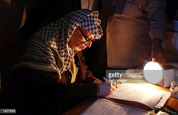 Palestinian leader Yasser Arafat works under a battery powered light inside his besieged compound September 23 2002 in the West Bank city of Ramallah...