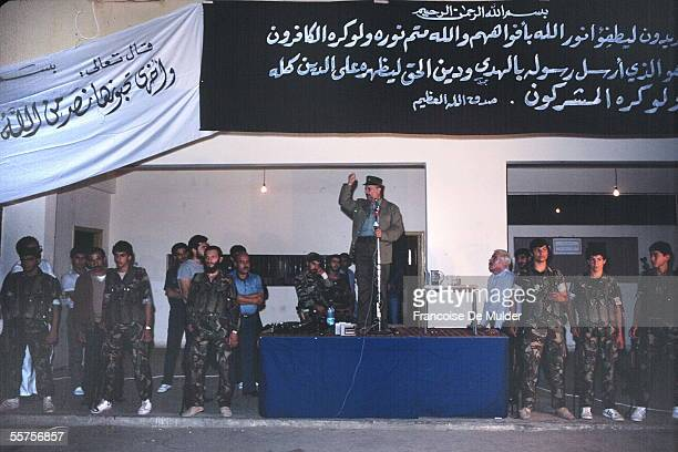 Palestinian Liberation Organization leader and later President of the Palestinian Authority Yasser Arafat raises his fist as he stands at a podium...