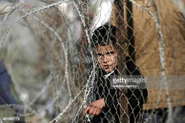 Palestinian little boy looks behind the wire as Palestinians wait for the crossing into Egypt at Rahaf border crossing between Egypt and the southern...