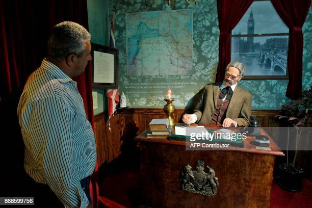 A Palestinian looks at a scene depicting the then British foreign secretary Arthur Balfour signing a declaration in which he says his government...