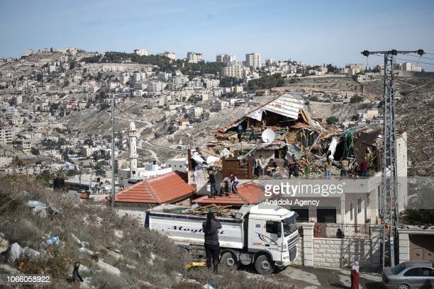 Palestinian Maghribi family collect their belongings amid ruins of their house after Israeli authorities demolished the top part of it in Jabal...