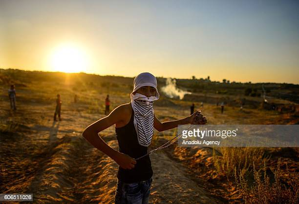 Palestinian makes preparation before throws stones t Israeli soldiers with a slingshot during a demonstration at Al Bureyc refugee camp in Gaza City...