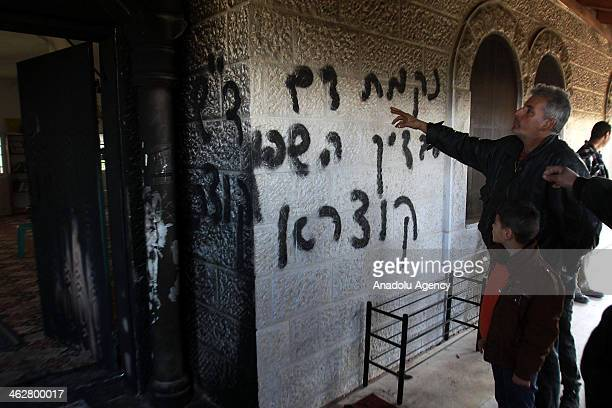 Palestinian man and his son are seen in the entrance to of the Ali Ibn Abi Talib mosque which is set fire by Jewish settlers caused partial damage to...