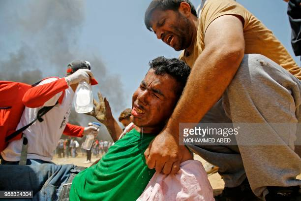 Palestinian man assists a wounded protestor during clashes with Israeli security forces near the border between Israel and the Gaza Strip east of...