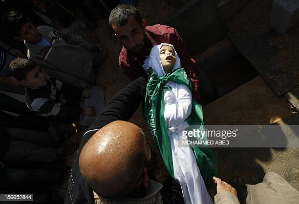 A Palestinian man barries the body of Tamer Abu Sefan three and a half years old during a funeral in the village of Beit Lahia in the northern Gaza...
