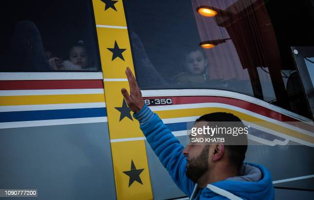 Palestinian man bids farewell to family members as they board a bus to cross to Egypt through the Rafah border crossing in the southern Gaza Strip,...