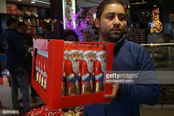 A Palestinian man carries a box of chocolates bearing an image of Santa Claus at a shop in Gaza City on December 22 as Christians prepare to mark...