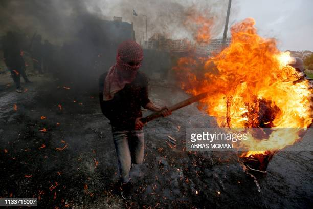 Palestinian man carries a burning tyre during clashes with Israeli forces following a demonstration marking Land Day near the Israeli Jewish...
