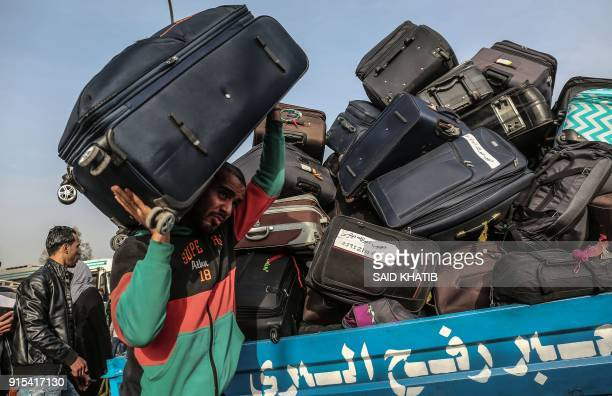 Palestinian man carries a suitcase as travelers wait for permission to cross into Egypt through the Rafah border crossing in the southern Gaza Strip...