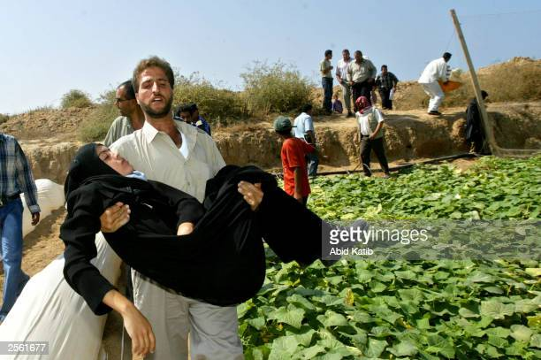 Palestinian man carries a woman suffering from fatigue while walking on a beach around an Israeli road block October 5 2003 in Gaza City Gaza Strip...