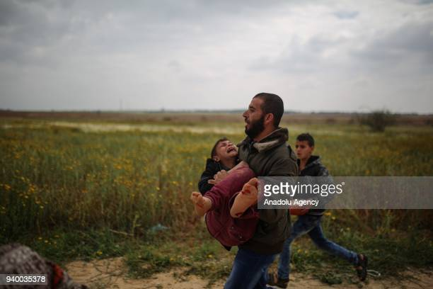Palestinian man carries a wounded boy after Israeli forces intervene the Palestinian protesters as they gather at Israel's border near Khan Yunis...