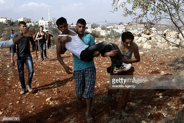 Palestinian man carries a wounded youth during clashes with Israeli soldiers following a confrontation between Palestinians and Jewish settlers in...