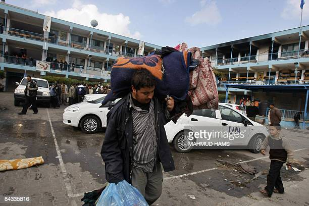 A Palestinian man carries blankets and mattress outside the UNrun school that was hit earlier today by an Israeli strike in Beit Lahia northern Gaza...