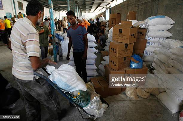 Palestinian man carries food aids with a wheelbarrow at a United Nations food aid distribution center in Rafah Gaza on September 28 2014 As part of...