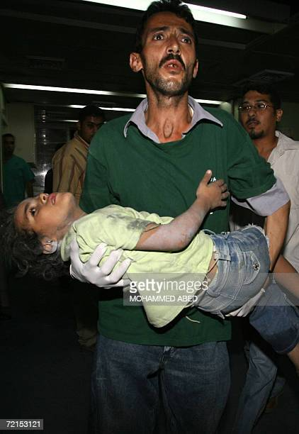 Palestinian man carries his injured boy into the alShifa hospital following an Israeli air strike on a house in Gaza City late 12 October 2006 An...