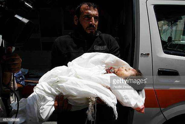 Palestinian man carries the body of Dalal Siam, a five-month-old child who was killed along with eight members of the Siam family after an Israeli...