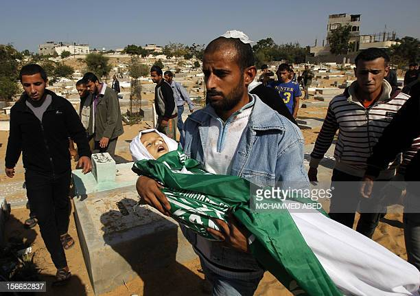 A Palestinian man carries the body of his son Tamer Abu Sefan three and a half years old during a funeral in the village of Beit Lahia in the...