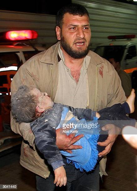 Palestinian man carries two-year-old wounded child, Mohamad Awni Kulab, into the Al-Najjar hospital, following an explosion on March 4, 2004 in Rafah...
