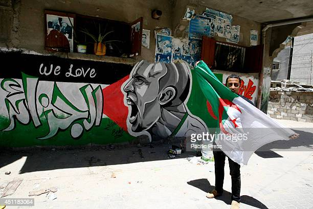Palestinian man carrying the flag of Algeria in front of graffiti wall in the Khan Yunis refugee camp in the southern Gaza Strip depicting football...