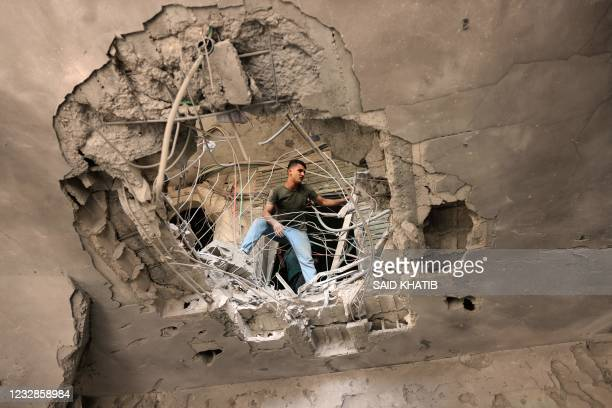 Palestinian man checks the damage caused by an Israeli air strike at the Islamic National Bank of the Palestinian Hamas movement in Khan Yunis, in...