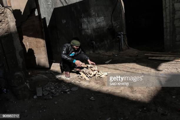 Palestinian man chops wood in the Rafah refugee camp in the southern Gaza Strip on January 17, 2018. The UN agency for Palestinian refugees faces its...