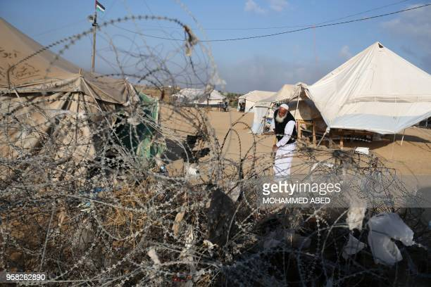 Palestinian man cleans near tents at a protest camp, east of Jabalia, in the northern Gaza Strip on May 14, 2018. - Palestinians readied for protests...