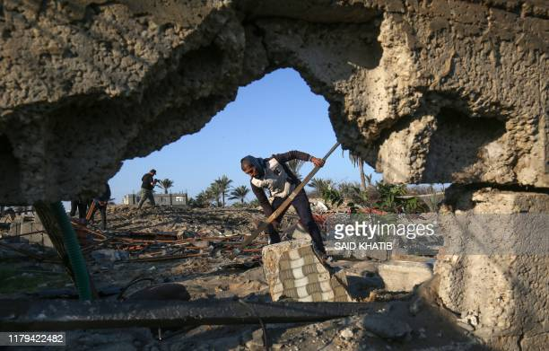 Palestinian man clears rubble from a building, damaged by an Israeli airstrike launched in response to rocket fire, in Khan Yunis in the southern...