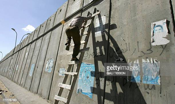 Palestinian man climbs over a makeshift ladder to cross Israel's eightmeterhigh concrete barrier in the West Bank village of alRam on the outskirts...