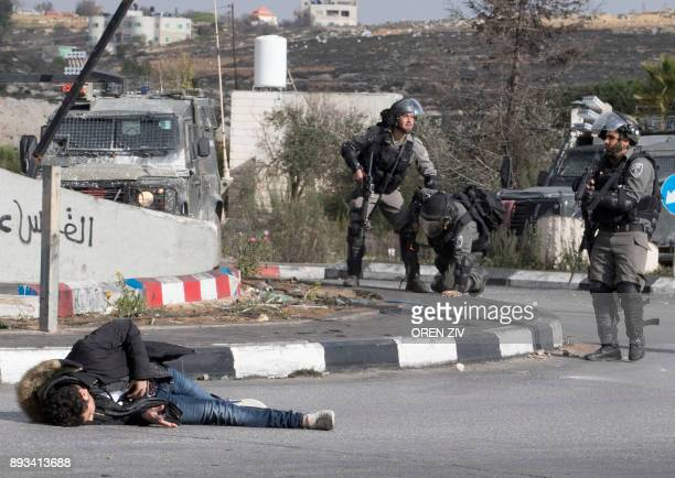 Palestinian man clutches his stomach after he was shot by Israeli soldiers in reaction to his stabbing attack on a soldier in the Israeli occupied...