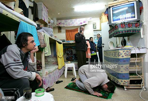 Palestinian man convicted of security offenses against Israel prays in his cell while another watches television February 10 2005 in the Nitzan...