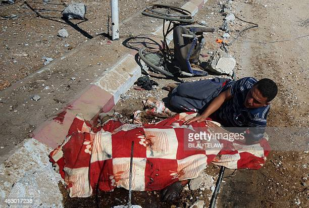 Palestinian man covers a dead body in Khuzaa near Khan Yunis in southern Gaza Strip on August 1 2014 A joint Palestinian delegation including Hamas...